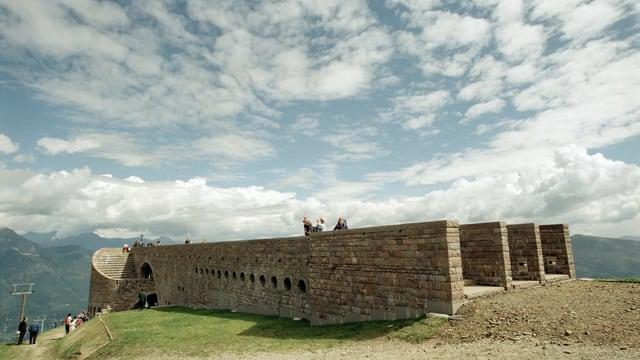 Ein flacher Backstein-Bau, mit einer Terrasse über die sich Menschen bewegen.