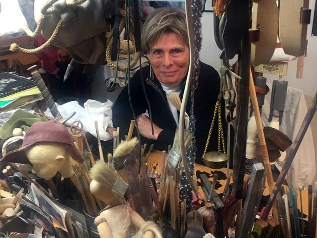 Eine Frau sitzt in ihrem Atelier voller Stoffe, Pinsel und anderer Utensilien.