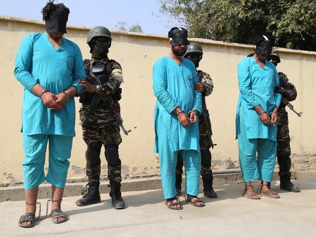 Afghanische Sicherheitskräfte führen verhaftete mutmassliche islamistische Attentäter ab.