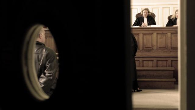 Blick durch einen Türspalt in einen Gerichtssaal.