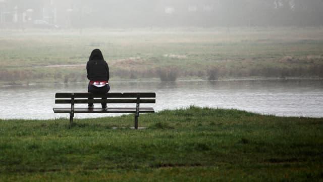 Frau alleine auf einer Bank sitzend.
