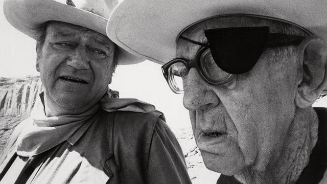 Ein Mann mit Cowboyhut spricht mit einem älteren Mann mit Brille und Augenklappe