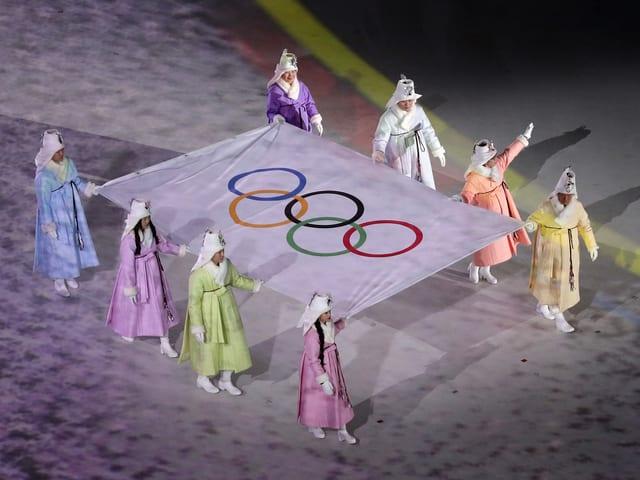 Frauen in südkoreanische Trachten tragen die Olympische Flagge