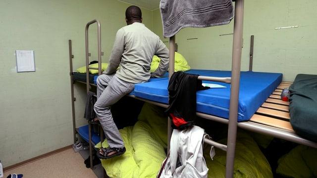 Asylbewerber sitzt oben auf einem doppelstöckigen Pritschenbett