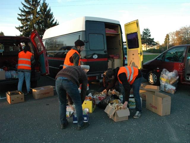 Aus einem VW-Bus entladen die jungen Menschen die Kartons aus.