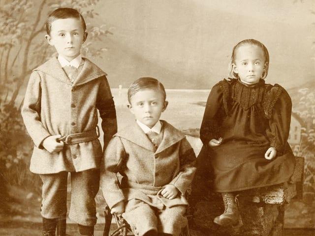 Zwei Jungen und ein Mädchen, alle Geschwister, schauen adrett gekleidet direkt in die Kamera.