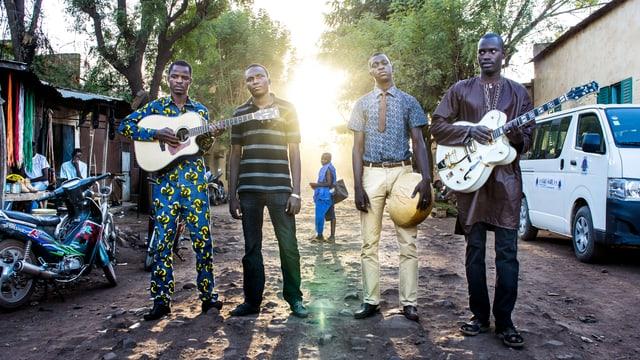 Vier Männer stehen in Mali auf einem holprigen Weg. Die Sonne scheint ihnen in den Rücken, sie halten ihre Instrumente in den Händen.
