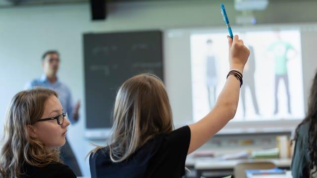 Schülerinn streckt im Unterricht Hand auf.