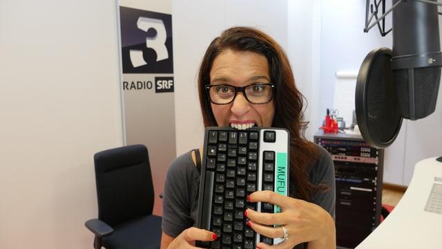 Rahel Giger im SRF 3 Studio; sie beisst in eine Computer-Tastatur.
