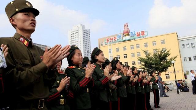 Umans en unifurma applaudeschan.
