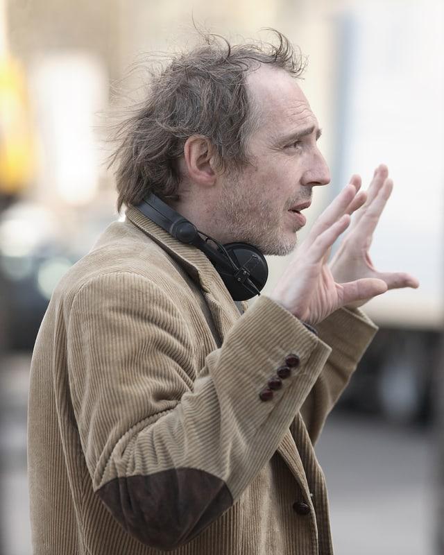 Arnaud Desplechin gestikuliert mit beiden Händen.