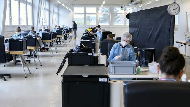 Menschen sitzen mit Schutzkleidung in einem grossen Raum.