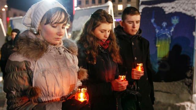 Zwei junge Frauen und ein junger Mann gedenken mit Kerzen in der Hand der toten Soldaten.
