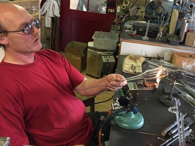 Ein Mann hält ein Stück Glas in eine Flamme und trägt eine Schutzbrille.