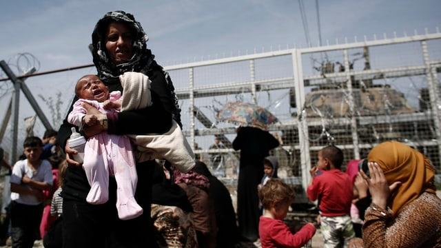Frauen und Kinder an einem Zaun