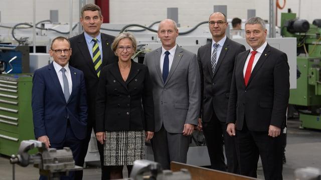 vier Männer und eine Frau posieren in einer Werkhalle