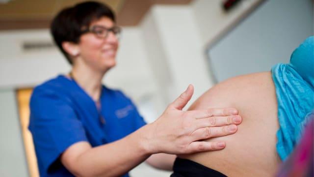 Eine Hebamme ertastet den Bauch einer Schwangeren im Spital Appenzell