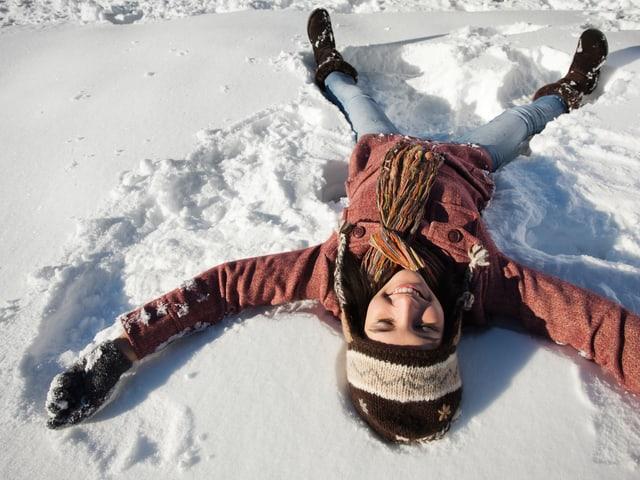 Frau liegt im Schnee. Sie wirkt glücklich und entspannt dabei.