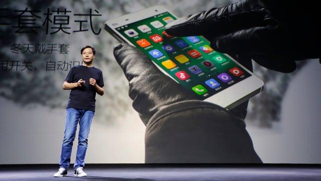 Chinese in Jeans und schwarzem Pullover vor einem Bild eines Smartphones.