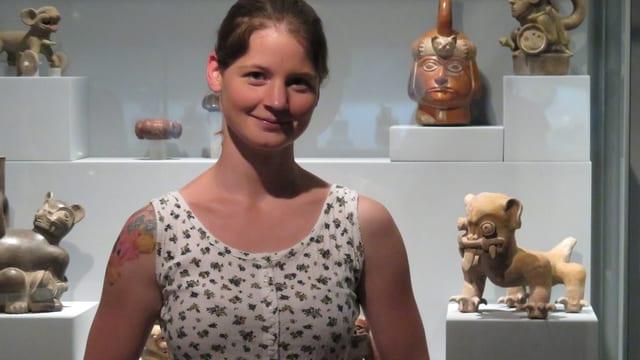 Junge Frau vor Museumsvitrine mit Figuren