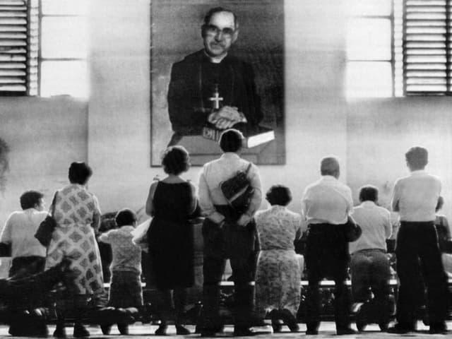 Menschen stehen vor einem Bild des Erzbischofs.
