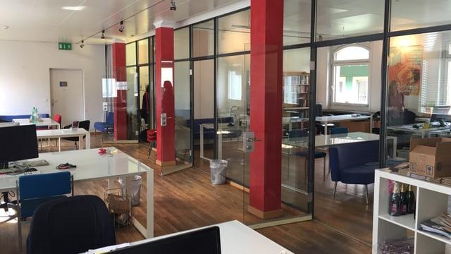 Ein langer, heller Raum mit mehreren Bürotischen
