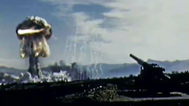 Eine Kanone und am horizont ist ein Atompilz zu sehen.