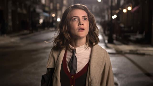 Eine junge Frau macht grosse Augen in einer dunklen Strasse
