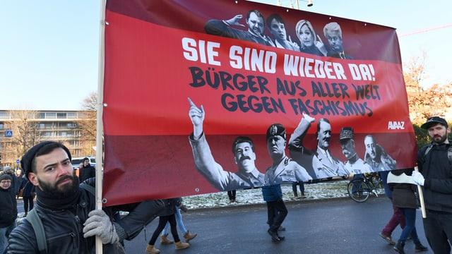 Plakat von Demonstranten mit Bildern von Faschisten wie Hitler und Mussolini.