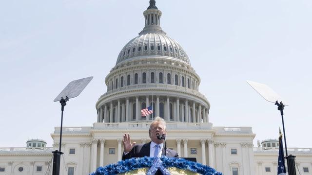 Trump spricht auf einem Podium vor dem Kapitol.