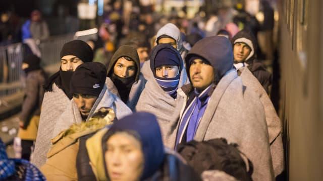 Junge Männer stehen nachts in Wolldecken gehüllt auf einem Bahnsteig.