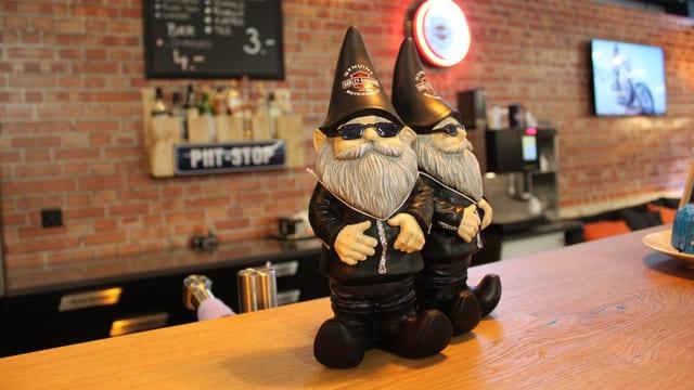 Aufnahme in einer Bar. Zwei Zwerge-Figuren mit Brillen stehen auf dem Tresen - sie wirken wie Rockerzwerge.