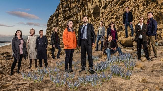 Cast der Serie am Strand vor einem Kliff