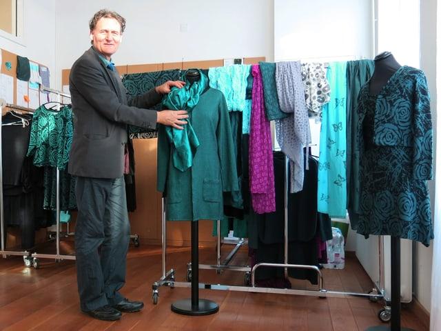 Ein Mann präsentiert Kleider an einer Puppe.