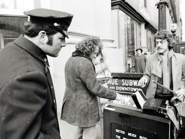 """Dieter Meier bezahlt kauft auf New Yorks Strassen Passanten die Wörter """"Yes"""" und """"No"""" ab. Ein Polizist beobachtet das Geschehen etwas argwöhnisch."""