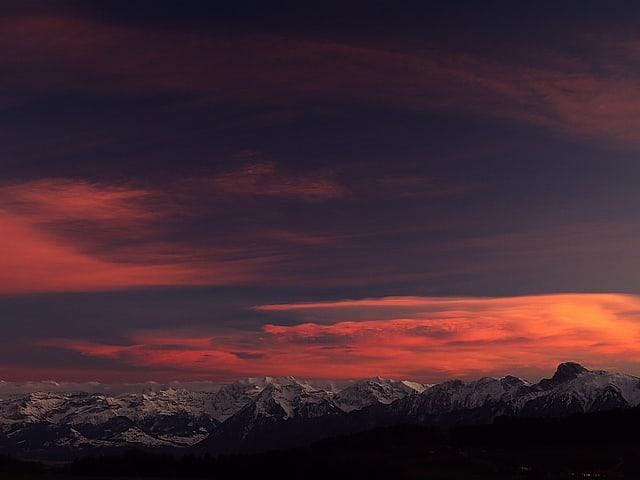 Schneeberge und blauviolett leuchtender Himmel, rosa Wolken.