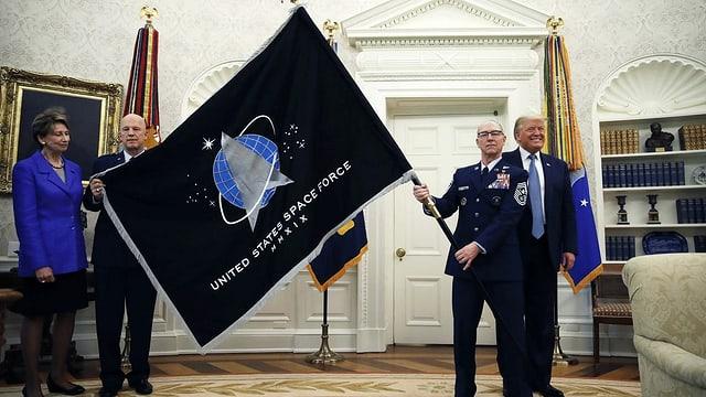 Das Oval Office im Weissen Haus. Ein Mann in Unoform schwenk eine riesige Fahne. Sie ist schwarz, darauf ein blauer Kreis und davor ein silbernes Dreieck. Im Hintergrund lacht Donald Trump.