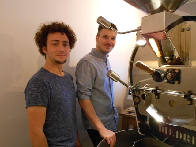 Zwei Männer stehen neben einer Maschine.