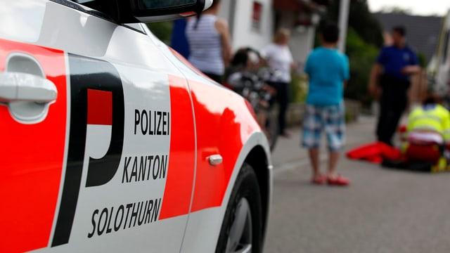 Polizeiauto in einer Quartierstrase, dahinter stehen Schaulustige und beobachten einen Unfall.