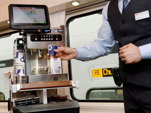 Minibar-Steward lässt an der modernen Kaffeemaschine einen Becher Kaffee heraus