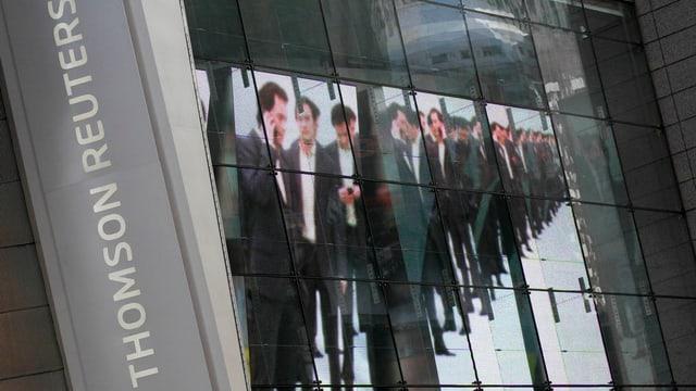 Thomson-Reuters-Logo, daneben ein Werbeplakat mit Businessmännern.