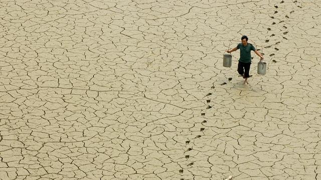 Chinesischer Bauer schleppt Kübel mit Wasser über ausgedörrte Erde.
