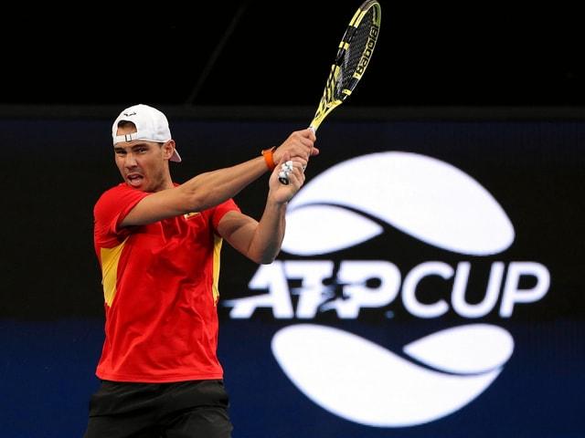 Rafael Nadal spielt eine beidhändige Rückhand vor dem ATP-Cup-Logo.