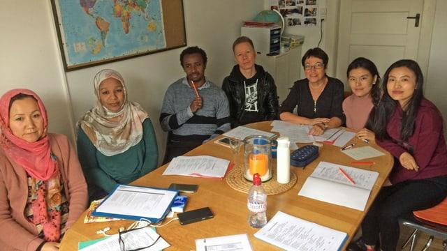 Asylbewerberinnen und -bewerber sitzen um einen Tisch, vor sich Schulhefte.