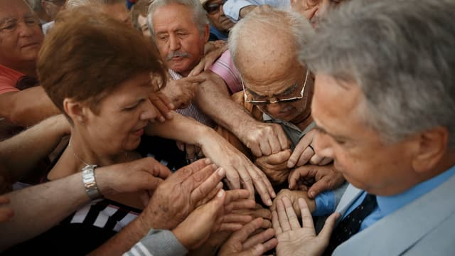 Pensiunads emprovan da survegnir in numer per entrar en ina banca ad Athen.