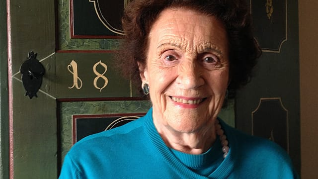 Ältere Frau in türkis-farbenem Pullover lächelt.