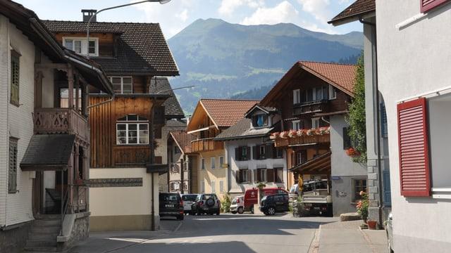 Casas en il center dal vitg da Schiers cun autos parcads davant.
