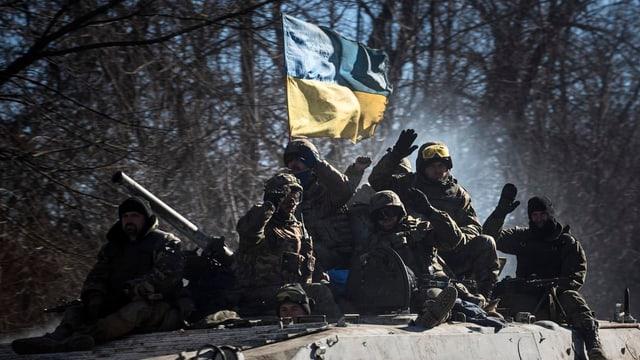Symbolbild: Soldaten sitzen auf einem fahrenden Panzer, es weht darauf eine ukrainische Flagge.