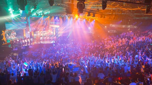 In einer grossen Halle schauen Tausende Menschen auf eine Bühne