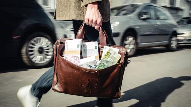 Symbolbild: Eine Person trägt eine Tasche, aus der Geldbündel quellen.